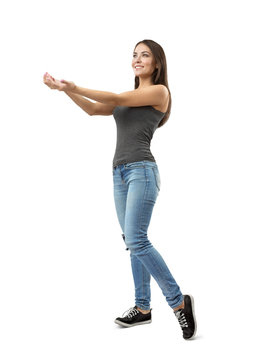 Young fit smiling woman in gray sleeveless top and blue jeans standing in half-turn holding out her hands with palms facing up on white background.
