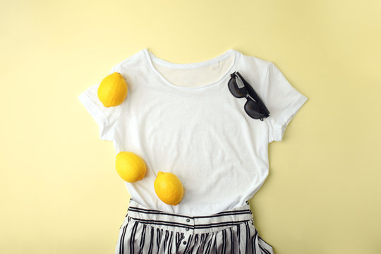 White shirt, sunglasses and lemons on yellow background. Women's stylish spring summer outfit. Trendy clothes. Flat lay, top view