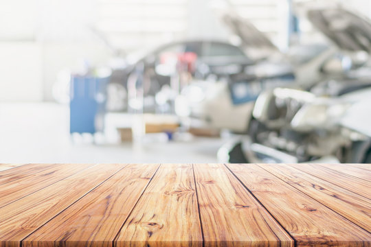 Wood table top on blurred Car Repair Services Center Blurred use us automobile maintenance technician repair background used us montage display or products design