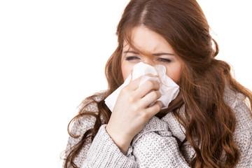 Sick freezing woman sneezing in tissue