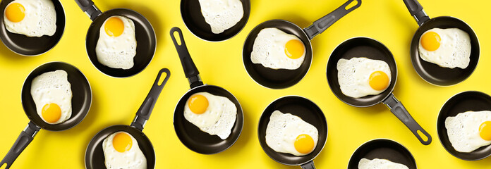 Creative food pattern with fried eggs on pans over yellow background. Top view. Creative pattern in...