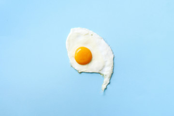 One fried egg on blue paper background. Creative food concept in minimal style. Top view
