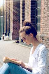 Eine junge Frau ließt ein Buch auf der Straße