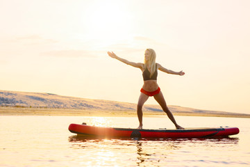 Woman doing yoga exercises on paddle board in the water