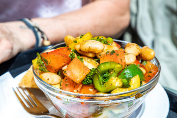 summer salad with tomatoes,beans,onions,paprika,oil,herbs in a glass bowl