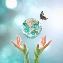 Earth day and go green concept with big green planet on people's hand with tree leaves  : Elements of this image furnished by NASA...