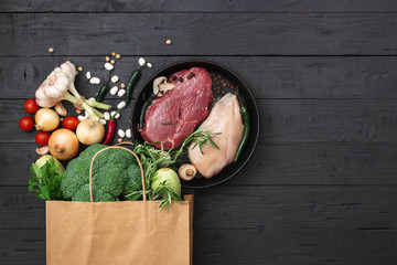 Grocery bag with healthy food on a wooden background top view