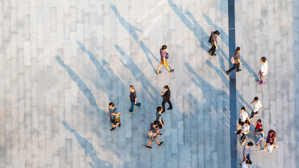 group of people walk on across the pedestrian concrete landscape in the city street (Aerial top view)