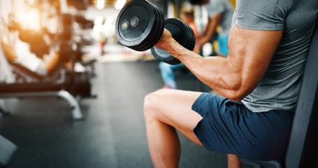 Determined handsome and young male working out in gym Fototapete