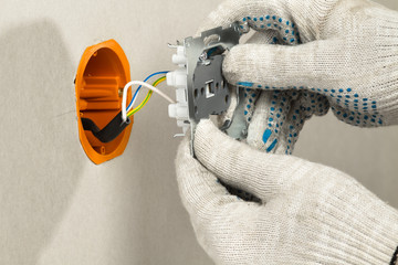 disassembled electrical outlet is in the hands of an electrician