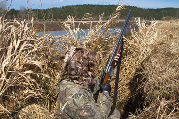 duck hunter hid in a hunting blind of reeds