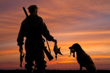 hunter and his dog with prey at sunset Wall mural