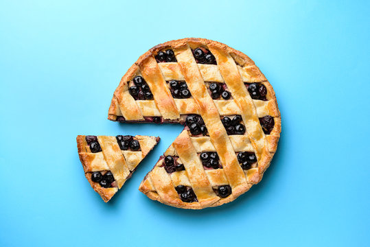 Tasty blueberry pie on color background