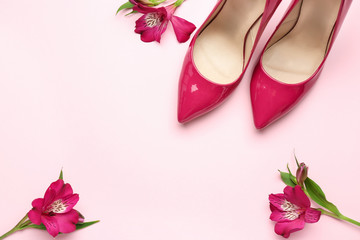 Stylish high heeled shoes on color background