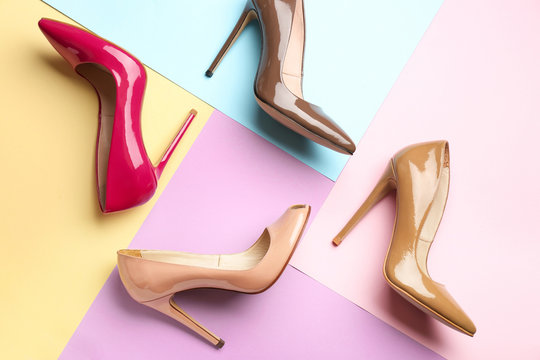 Different stylish high heeled shoes on color background