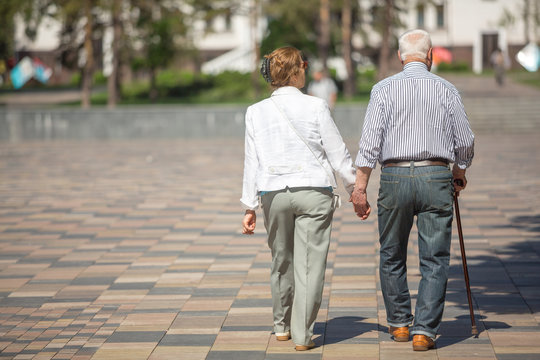 Senior adults walking in a park holding hands