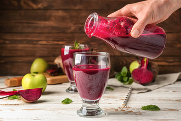 Woman pouring fresh beet smoothie into glass on table