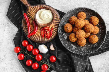 Plate with tasty falafel balls and sauce on light table Wall mural