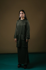 Portrait of a tall, slim and beautiful Indonesian Muslim woman in an olive green silk traditional dress (baju kurung) in a studio. She is standing elegantly against a brown background and posing.