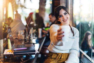 Smiling woman stretching paper cup of coffee into camera. Girl offers to drink coffee to viewer during break.