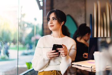 Young smiling woman sitting in cafe at table,looking out window, holding smartphone, listening to music on headphones. Lifestyle.