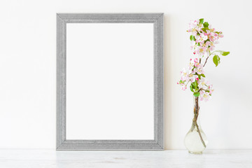 Fresh branches of pink white apple blossoms in glass vase on table at light gray wall. Empty place for inspirational, emotional, sentimental text, lovely quote or sayings in frame. Front view.