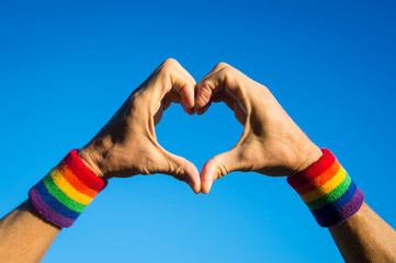 Gay athlete making hand heart with gay pride rainbow colors wristbands against bright blue sky