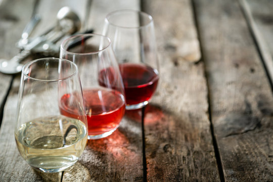 WIne tasting concept - red, rose and white wine in glasses on wood background
