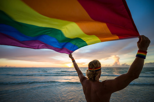 Man with blond hair wearing gay pride headband and wristbands holding a fluttering rainbow flag on the beach at sunrise