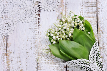 Wall Murals Lily of the valley white wooden background with a bunch of lily of the valley flowers