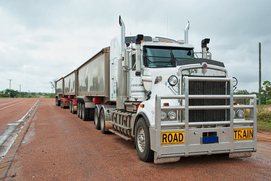 Road train used for long freight transport in Australia. Called road train for how long they are. Can measure more than 50 meters long Super long white goods truck with three containers.
