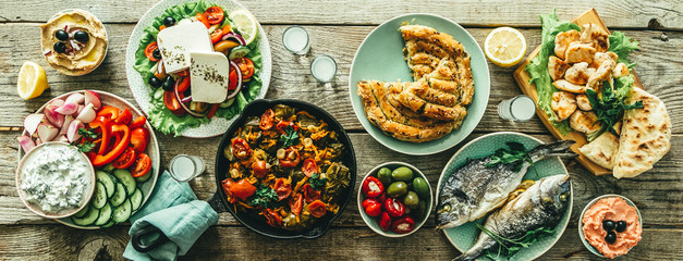 Selection of traditional greek food - salad, meze, pie, fish, tzatziki, dolma on wood background,...