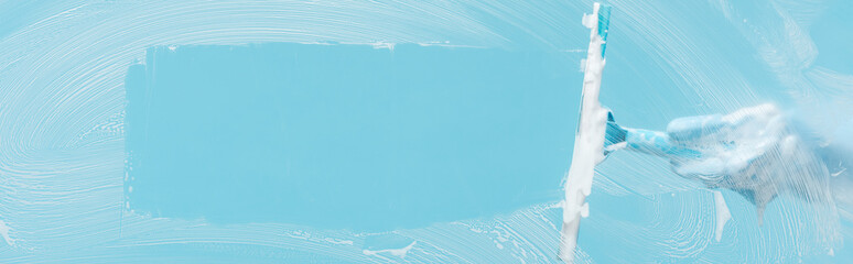 panoramic shot of woman in rubber glove cleaning glass with squeegee on blue background