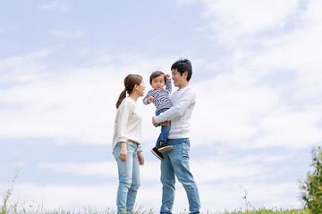 若い家族、青空背景 Wall mural