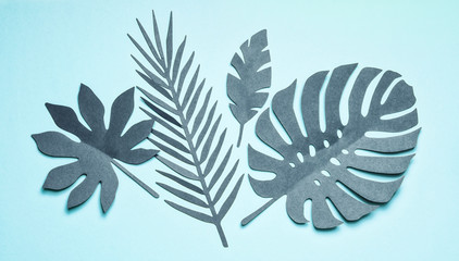 Wall Mural - Turquoise tropical leaves composing on pastel blue background, top view, flat lay. Creative botanical layout.