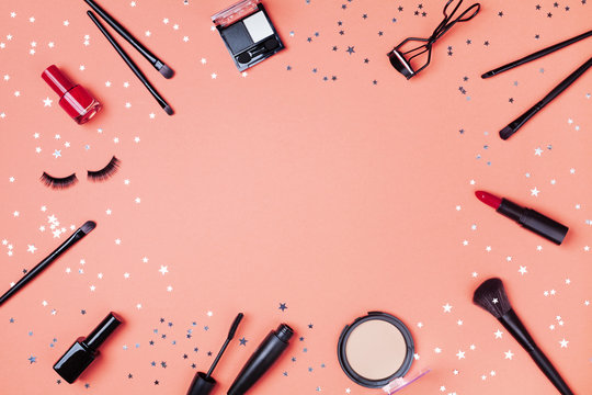 Beauty products and cosmetic for woman makeup decorated star confetti on coral table top view. Flat lay style.