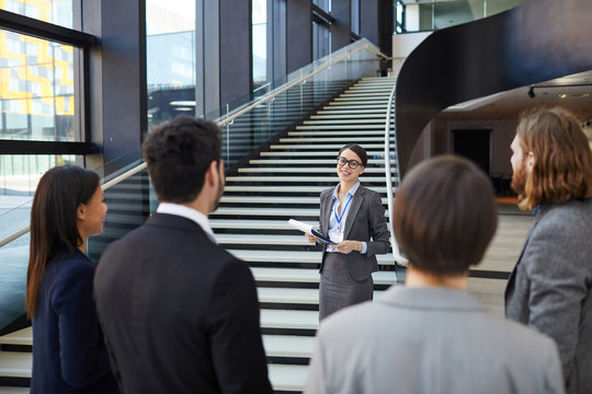 Smiling confident business forum guide with badge on neck standing on stairs and holding clipboards with files while giving tour to participants
