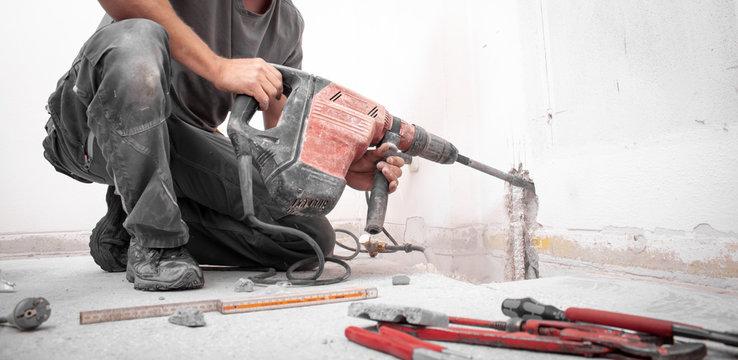 Installateur stemmt Loch mit Hilti Bohrhammer in die Wand auf der Baustelle