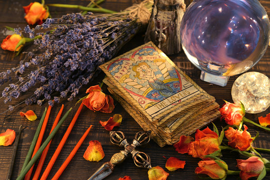 Tarot cards with magic crystal ball, candles and lavender flowers.