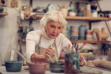 Nice aged woman putting a brush into paint