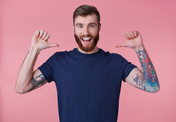 Portrait of young happy attractive red-bearded young guy , wearing a blue t-shirt, broadly smiling, enjoy himself, with arms raised up and pointing fingers at himself isolated over pink background.