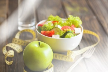 Salad in white bowl, fresh green apple and tape measure on dark wooden background. Diet and weight loss concept.