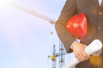 Man architect in suit holding helmet in hand