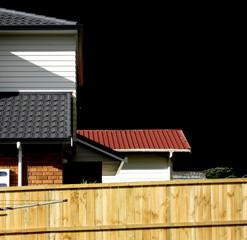 Black sky over tiled roof houses