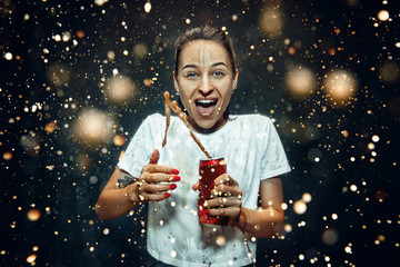 Fototapeta Woman drinking a cola at studio. Young smiling happy caucasian girl opening can with cola and enjoying the spray. Advertising image about favourite drink. Lifestyle and human emotions concept.