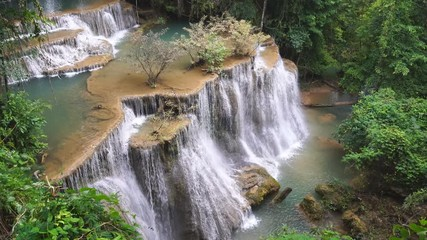 Wall Mural - Waterfall flow standing with forest enviroment from high angle view in thailand, called Huay orHuai mae khamin in Kanchanaburi Provience, Zoom out.