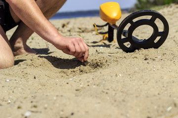 Obraz A man takes a coin found in the sand with a metal detector - fototapety do salonu