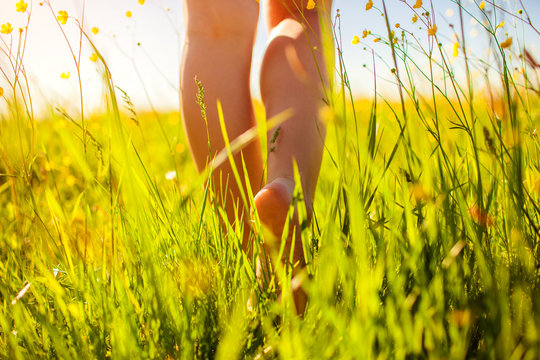 Young woman walking in spring field at sunset among fresh grass and flowers barefooted