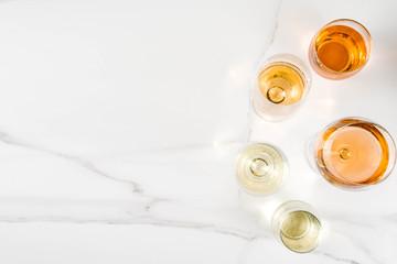 Trendy orange wine, with white wine in different glasses, white concrete background copy space