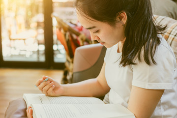 Cute Asian young girl teen doing homework paper warm vintage color tone